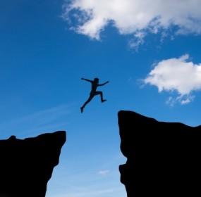 l-uomo-salta-attraverso-il-divario-tra-hill-man-saltando-sulla-scogliera-sullo-sfondo-del-tramonto-idea-di-business-concept_1323-99